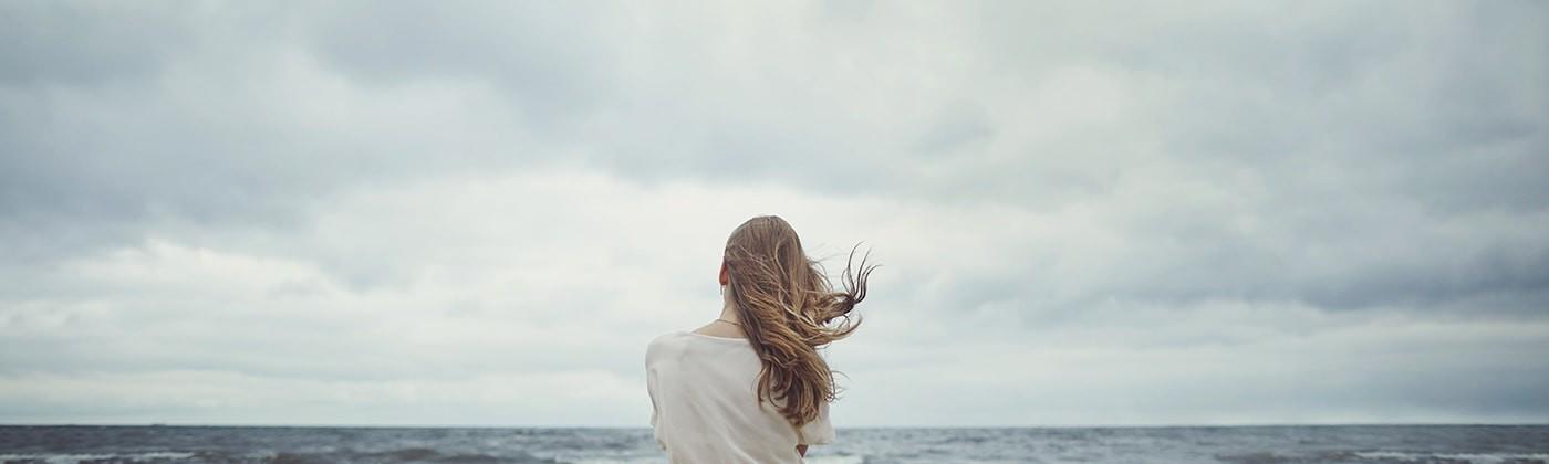 Sad woman sitting on beach