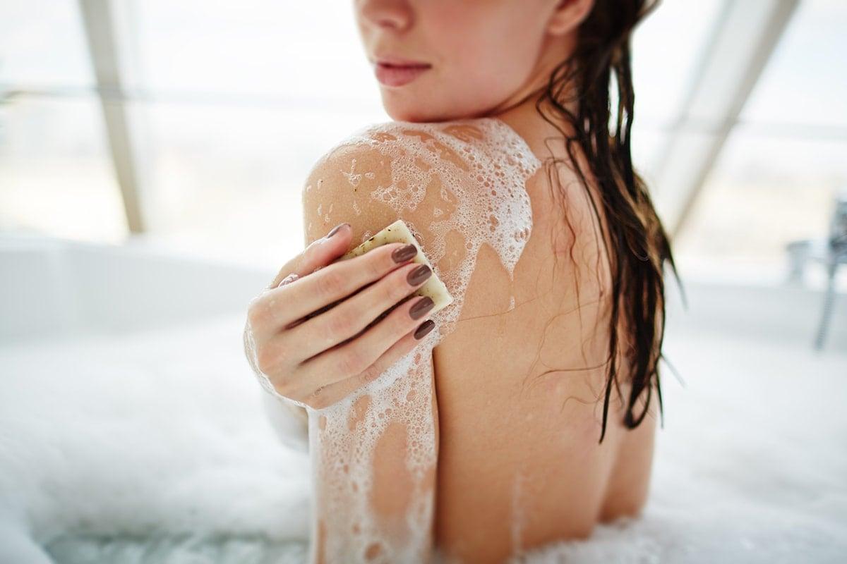 Woman washing her skin in bath