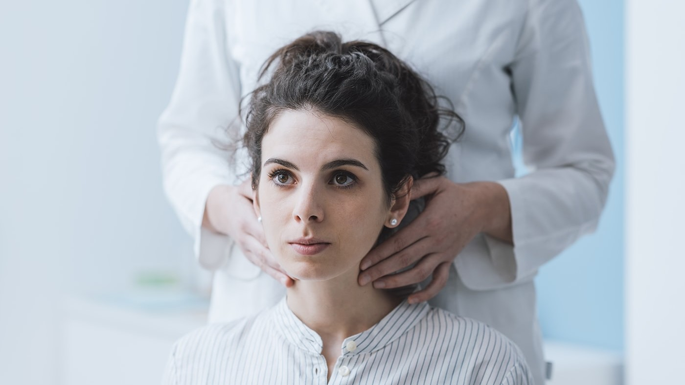 Woman having her thyroid checked by doctor