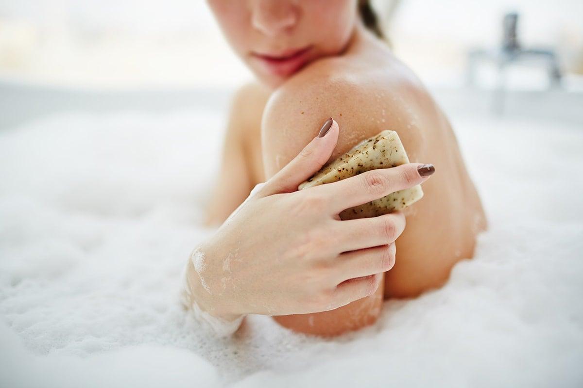 Woman washing skin in bath