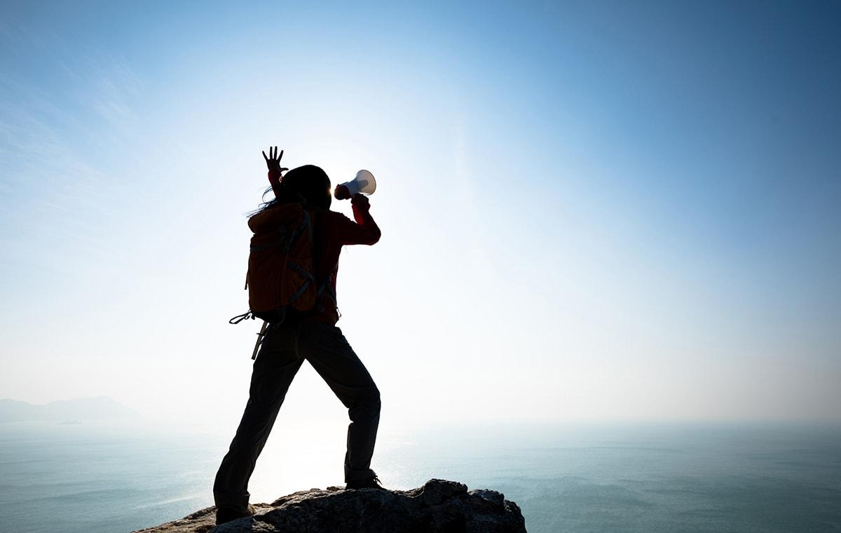 Woman shouting using loudspeaker on mountain