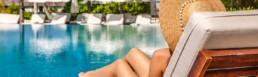 Woman sitting in the sun beside pool