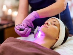 Woman receiving UV light therapy on face