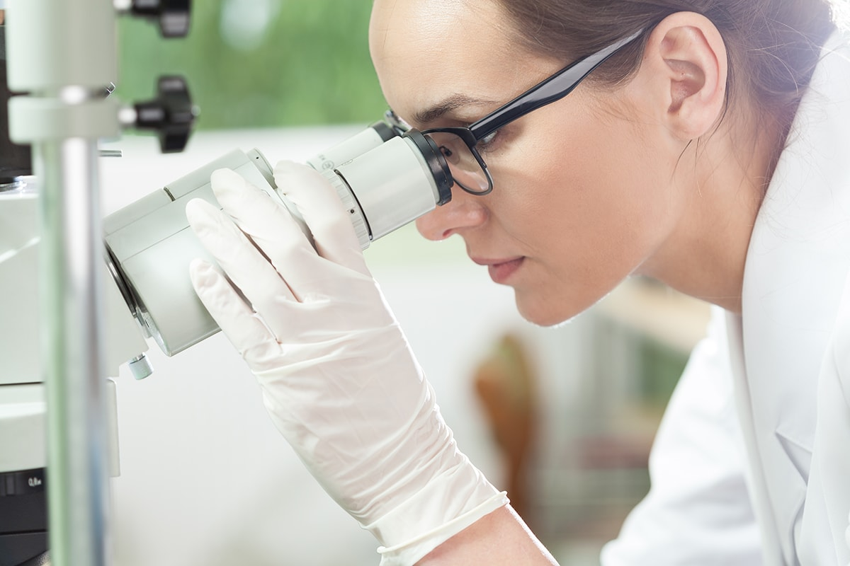 Woman looking at candida in microscope