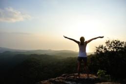Woman celebrating on top of mountain
