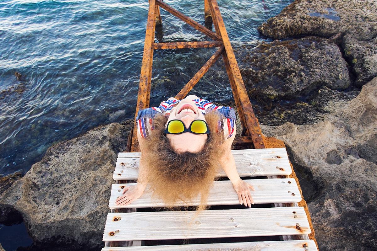 Happy woman sitting on dock