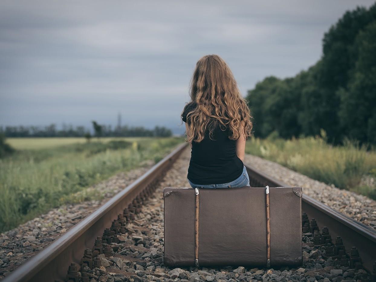 Sad girl sitting on suitcase on train tracks