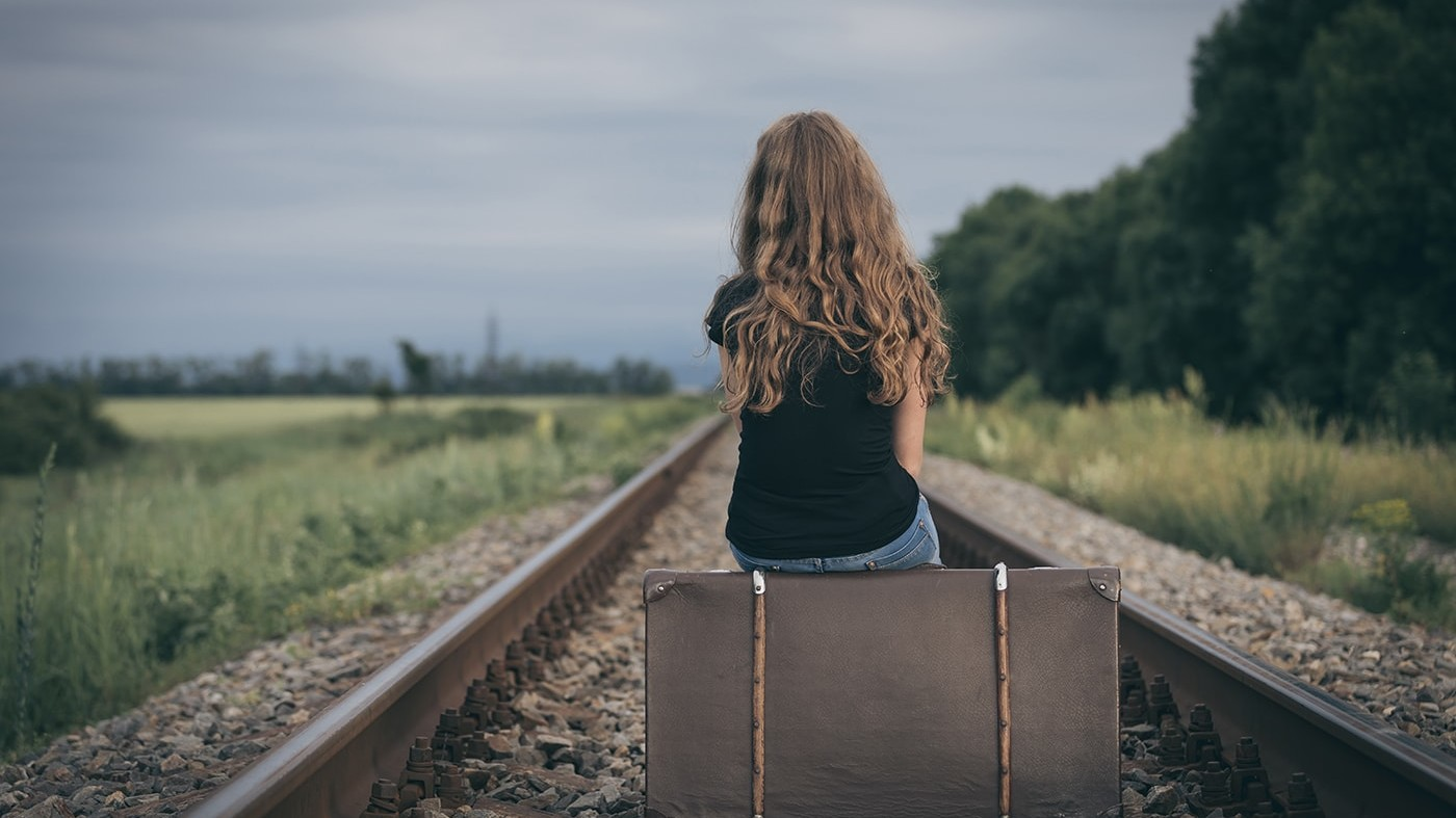 Sad girl sitting on suitcase on train tracks