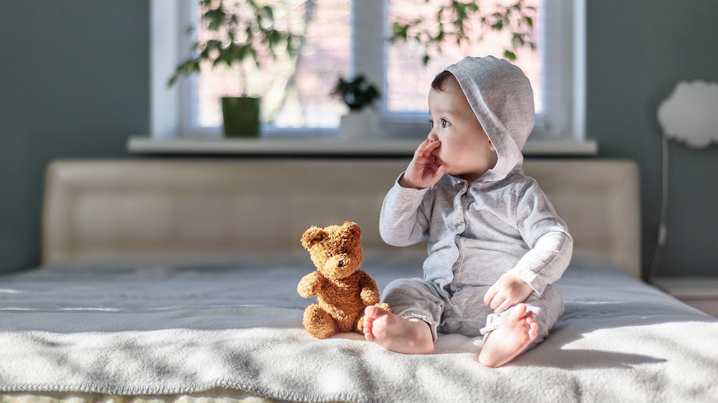 Baby sitting on bed with teddy bear