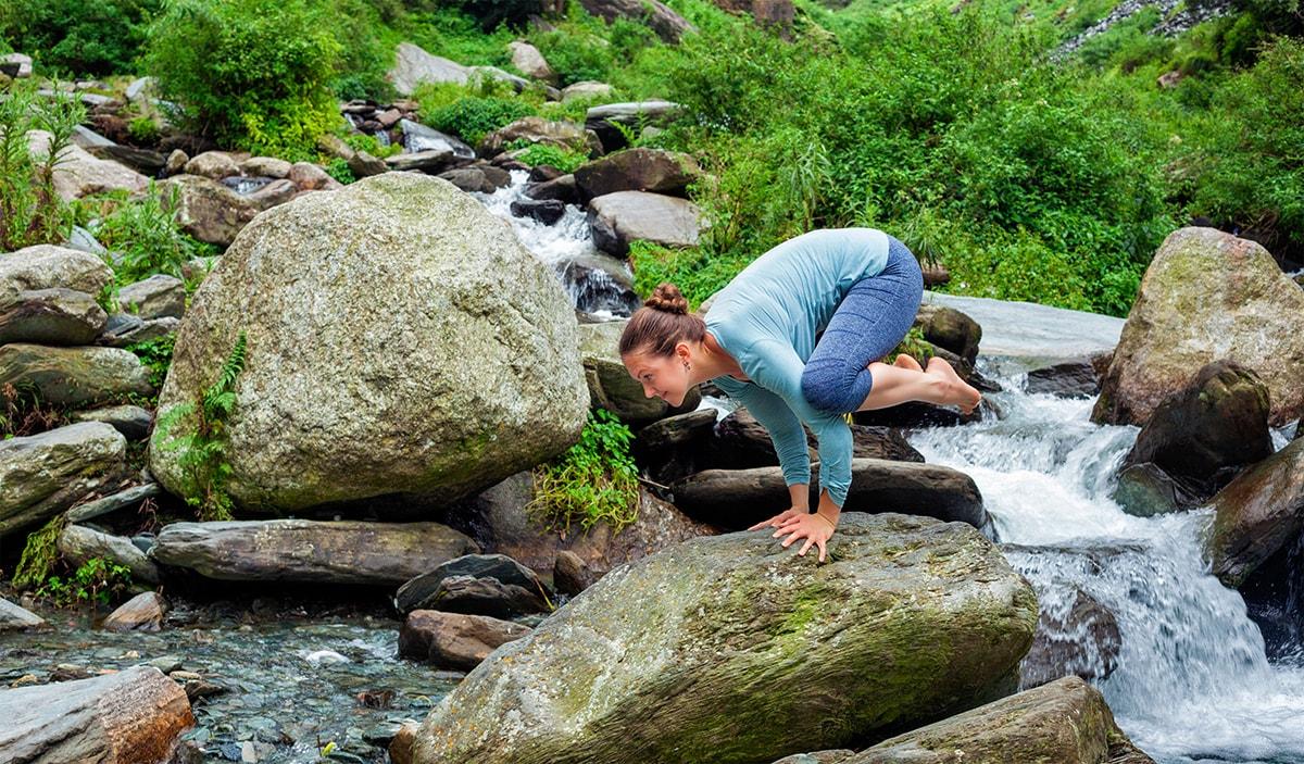 Woman balancing on rock doing yoga