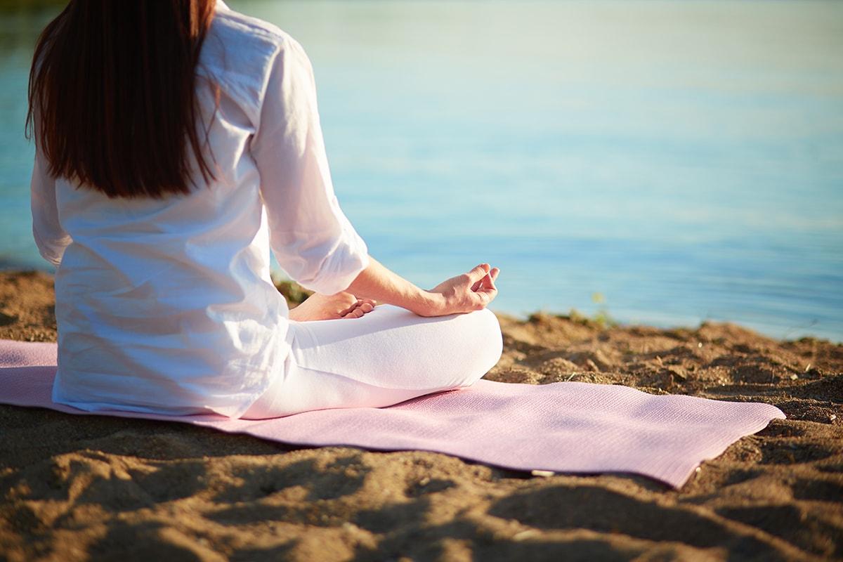 Woman sitting on mat on beach