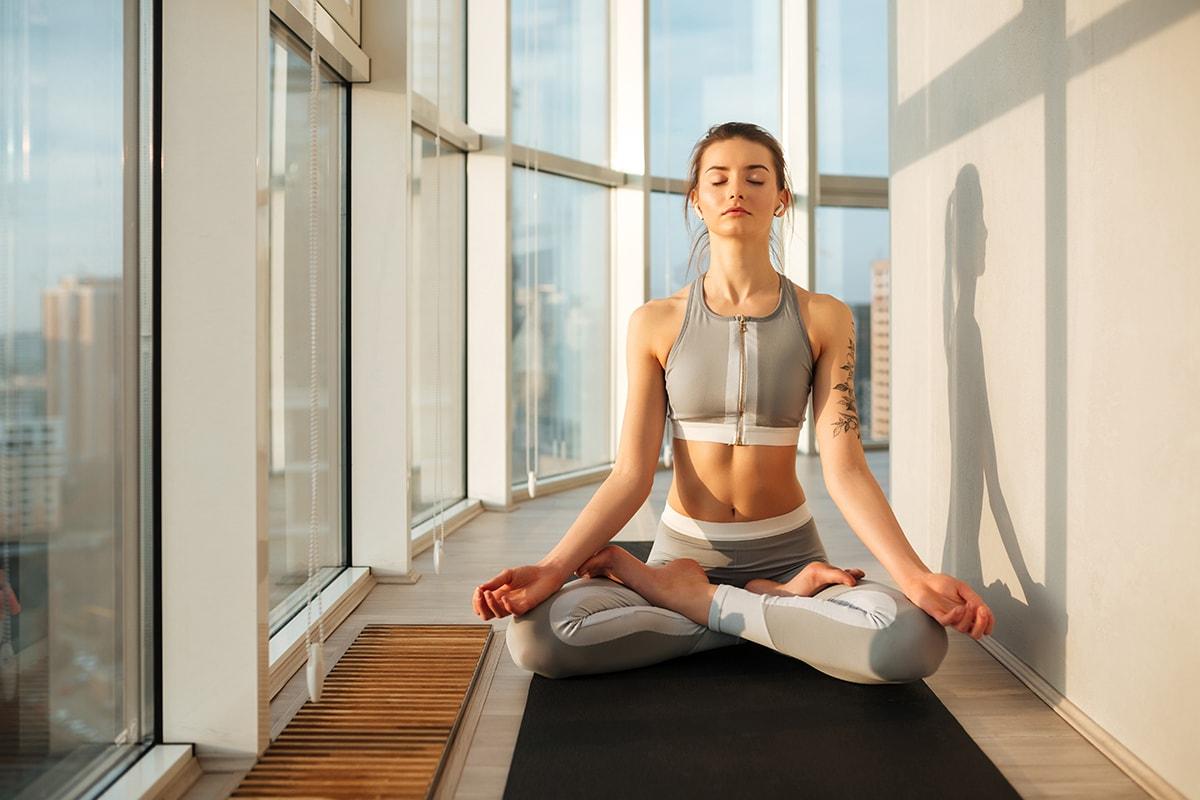 Woman meditating near big windows