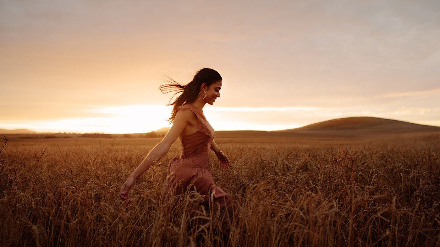 Thriving woman in field at sunset
