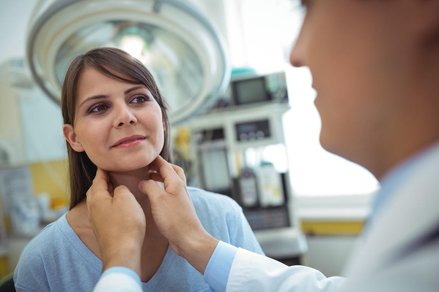 Doctor examining woman's thyroid