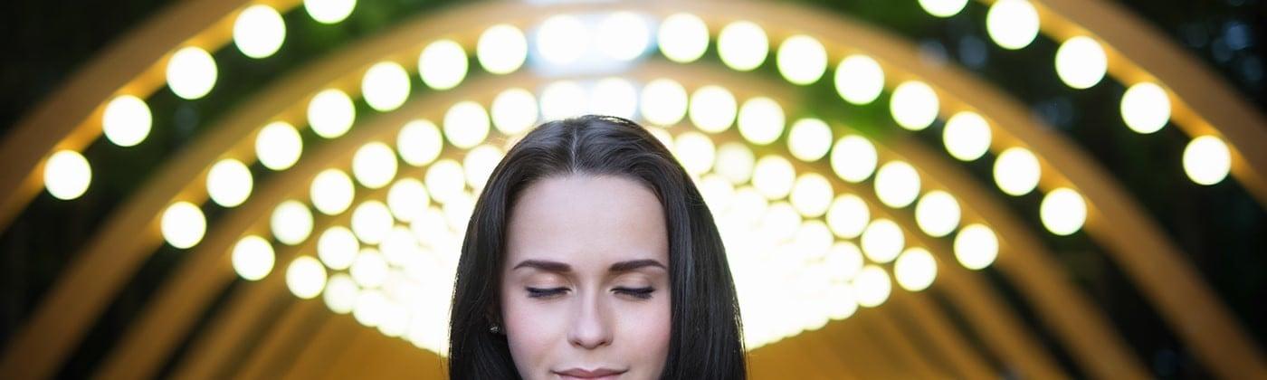 Woman thinking under light bulbs