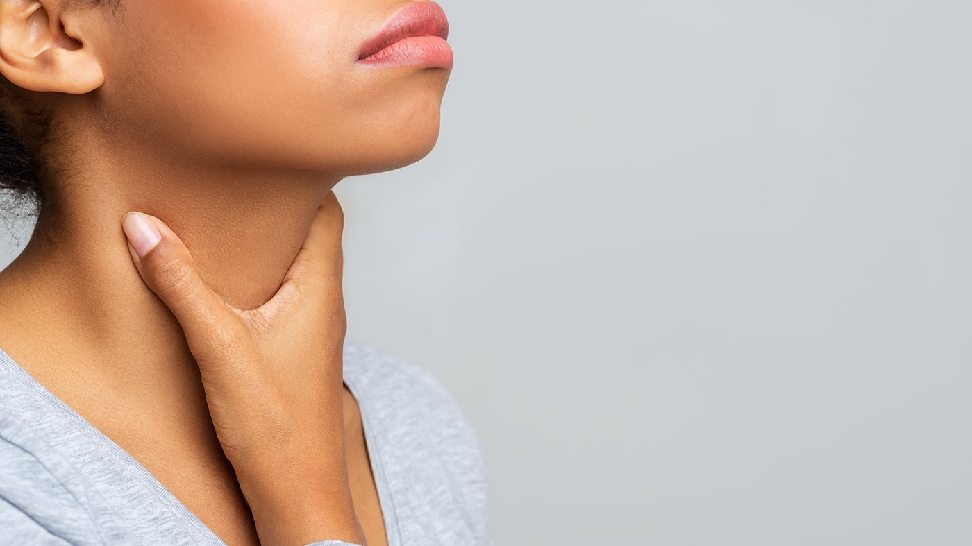 Woman holding her sore throat possibly with strep