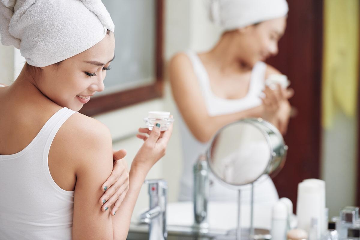 Woman applying skin lotion with zinc