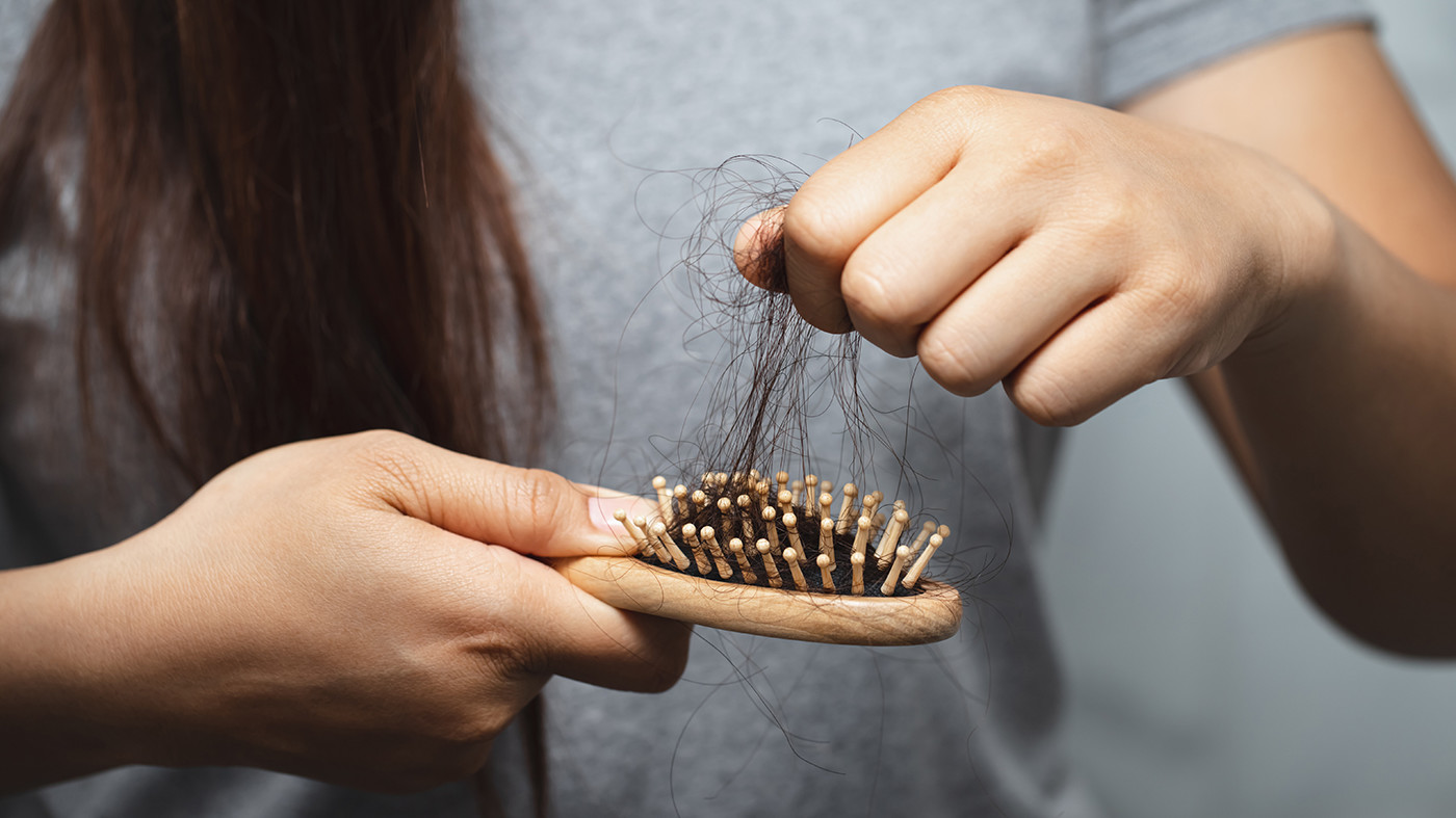 Woman with hair loss pulling hair strands out of brush