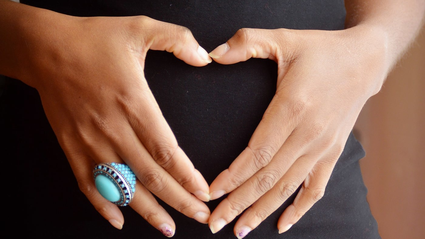 Pregnant woman with hands in heart shape over stomach