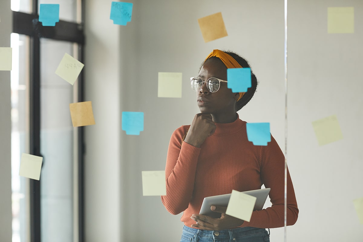 Woman thinking about where to start with skin rashes while looking at post it notes
