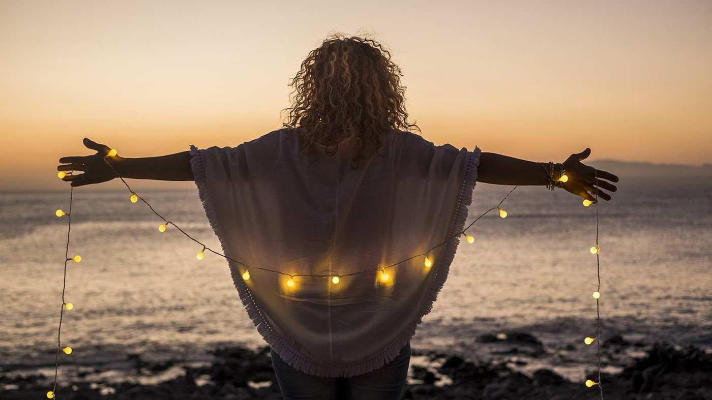 Motivated woman on beach at sunset with lights