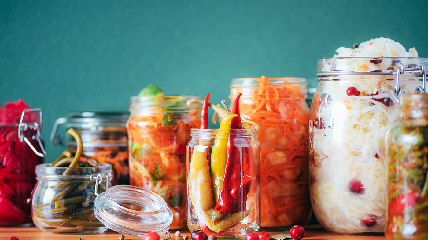 Probiotics food background. Korean carrot, kimchi, beetroot, sauerkraut, pickled cucumbers in glass jars. Winter fermented and canning food concept. Banner with copy space.
