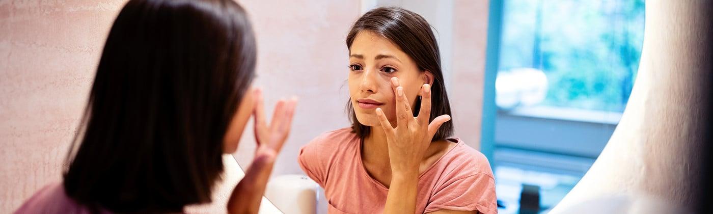 Worried woman looking in mirror at skin rash